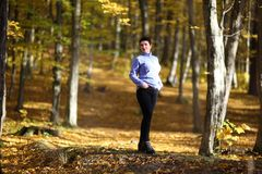 La donna matura piacevole sta su un fondo dell'autunno giallo Donna matura della foresta di autunno Immagine Stock