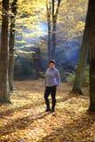 La donna matura piacevole sta su un fondo dell'autunno giallo Donna matura della foresta di autunno Immagini Stock