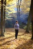 La donna matura piacevole sta su un fondo dell'autunno giallo Donna matura della foresta di autunno Fotografie Stock