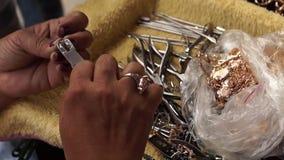 La donna matura ripara la catena del braccialetto con la pinza video d archivio