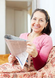 La donna matura sorridente legge il giornale Immagini Stock