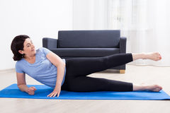 La donna matura sportiva esile che fa l'allungamento si esercita sulla stuoia di yoga Fotografia Stock