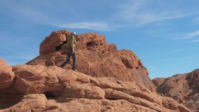 La donna matura sportiva scende con attenzione le rocce rosse del canyon archivi video