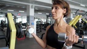 La donna matura sportiva sta facendo l'esercizio del bicipite con le teste di legno in palestra archivi video