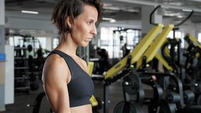 La donna matura sportiva sta facendo l'esercizio del bicipite con le teste di legno in palestra video d archivio