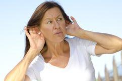 La donna matura sta ascoltando molto attentamente immagini stock libere da diritti