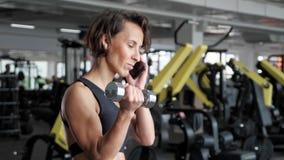 La donna matura sta facendo l'esercizio del bicipite con le teste di legno in palestra e telefono parlante stock footage