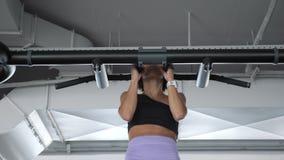 La donna matura sta facendo tirata-UPS con una presa stretta in palestra Concetto di sport video d archivio