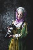 La donna medievale tiene la macchina fotografica di SLR fotografia stock libera da diritti