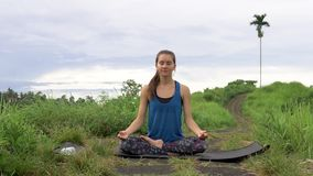 La donna medita nella posa Ardha Padmasana di yoga stock footage