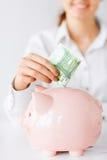 La donna mette gli euro contanti nel grande porcellino salvadanaio Fotografie Stock Libere da Diritti