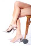 La donna mette i pattini che si siedono una presidenza Immagini Stock