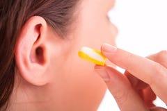 La donna mette i tappi per le orecchie nell'orecchio Immagine Stock