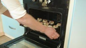 La donna mette il riparo con la cottura nel forno Corra la macchina fotografica sulle rotaie archivi video