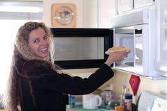 La donna mette l'alimento in forno Fotografie Stock
