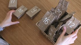 La donna mette le borse del calendario di arrivo di natale nel canestro di vimini Mani del primo piano video d archivio
