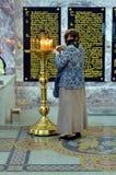 La donna mette le candele in chiesa Fotografie Stock
