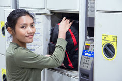 La donna mette lo zaino all'armadio della sicurezza Fotografie Stock Libere da Diritti