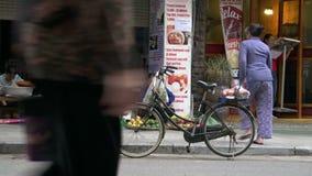 La donna mette la sua bici giù e cammina al mercato di strada nella città di Hanoi archivi video