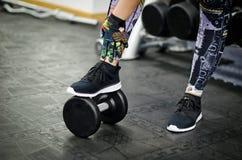 La donna mette la sua gamba sul dumbell Fotografie Stock Libere da Diritti