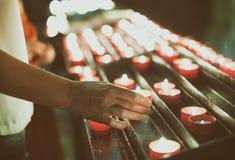 La donna mette una candela Immagini Stock