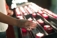 La donna mette una candela Fotografie Stock Libere da Diritti