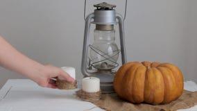 La donna mette una candela su una tavola accanto ad una zucca e ad una lanterna video d archivio