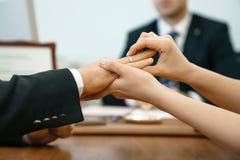 La donna mette una fede nuziale in un'anagrafe per un uomo Primo piano delle mani e di matrimonio contro lo sfondo del maste di c Immagini Stock