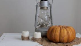 La donna mette una lanterna su una tavola accanto ad una zucca ed alle candele video d archivio