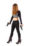 La donna minacciosa e sexy con le pistole sta camminando Fotografie Stock
