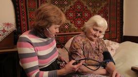 La donna misura l'impulso anziano stock footage