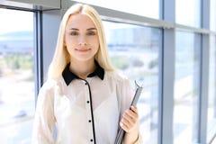 La donna moderna felice di affari con il rapporto finanziario è nel corridoio dell'ufficio immagini stock