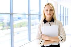 La donna moderna felice di affari con il rapporto finanziario è nel corridoio dell'ufficio Fotografia Stock