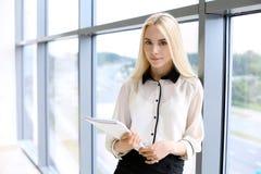 La donna moderna felice di affari con il rapporto finanziario è nel corridoio dell'ufficio immagine stock