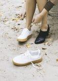 La donna moderna sta cambiando le sue scarpe per le scarpe da tennis sul parco, piedi femminili Fotografie Stock