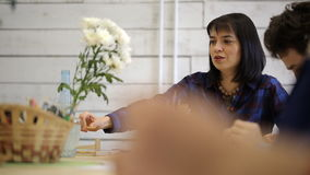 La donna mora e nero-osservata si siede alla tavola, tiene la matita e le discussioni stock footage