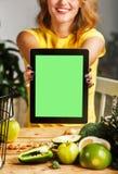 La donna mostra la compressa al tavolo da cucina fotografia stock libera da diritti