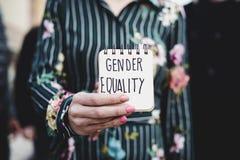 La donna mostra il blocco note con l'uguaglianza di genere del testo immagine stock libera da diritti
