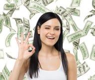 La donna mostra il segno giusto Le note del dollaro stanno cadendo sopra fondo isolato Fotografie Stock Libere da Diritti