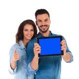 La donna mostra okay dietro l'uomo che mostra lo schermo della compressa Immagini Stock