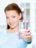 La donna mostra un vetro di acqua Immagini Stock Libere da Diritti