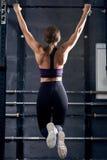 La donna muscolare che fa la tirata aumenta nella palestra di Crossfit Immagine Stock