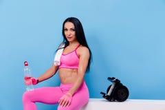 La donna muscolare ha un resto e tiene la bottiglia dell'acqua fotografie stock