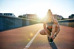 La donna muscolare lega le sue scarpe da corsa sul ponte Immagine Stock