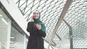 La donna musulmana graziosa in un hijab con uno zaino va al centro commerciale ed ai colloqui sul telefono, Mo lento video d archivio
