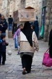 La donna musulmana trasporta la casella sulla sua testa Fotografia Stock Libera da Diritti