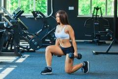 La donna negli sport di modo copre l'addestramento, facente gli affondo si esercita con le teste di legno nella palestra immagini stock libere da diritti