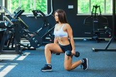 La donna negli sport di modo copre l'addestramento, facente gli affondo si esercita con le teste di legno nella palestra fotografia stock libera da diritti