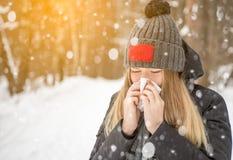 La donna nel legno nella sciarpa di nevicata che starnutisce e che usando un tessuto Immagini Stock Libere da Diritti