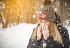 La donna nel legno nella sciarpa di nevicata che starnutisce e che usando un tessuto, ritratto, cappuccio del bubo con la bandier Fotografia Stock